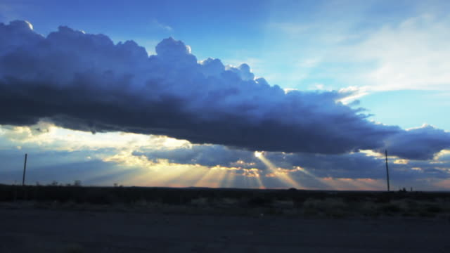 Storm cloud formation with bright sun rays shining through