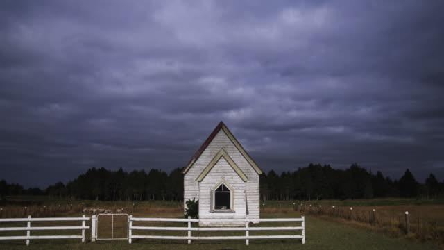 vídeos y material grabado en eventos de stock de ws t/l storm cloud moving over small church / kaipara, auckland, new zealand - desgastado por el tiempo