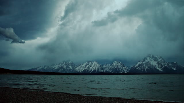 TIME LAPSE WIDE SHOT storm clouds and rain over snowy Grand Teton and Jackson Lake, Wyoming