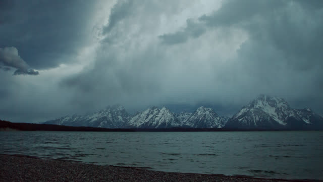 TIME LAPSE LONG WIDE SHOT storm clouds and rain over snowy Grand Teton with Lake Jackson in foreground, Wyoming