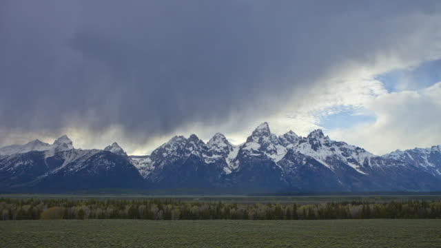 TIME LAPSE WIDE SHOT storm clouds and rain over snowy Grand Teton with plains in foreground, Wyoming