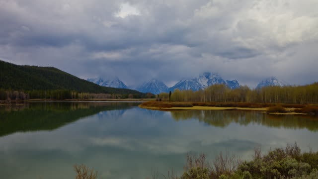 time lapse wide shot storm clouds and reflections over snake river at oxbow bend with snowy tetons in background, wyoming - スネーク川点の映像素材/bロール