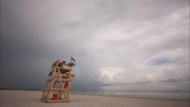 storm clouds and wind send swimmers running from the beach and batters a lifeguard at his station. - tampa stock videos & royalty-free footage