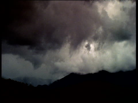 Storm clouds billow over mountains and bush, rain sweeps in and light fades, Australia