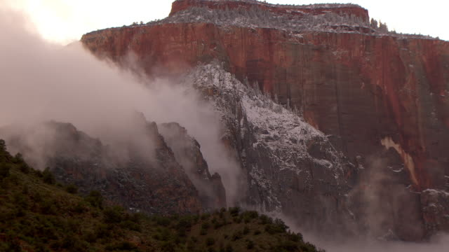 storm clouds clearing from mountain peak with light dusting of snow - zion national park stock videos & royalty-free footage