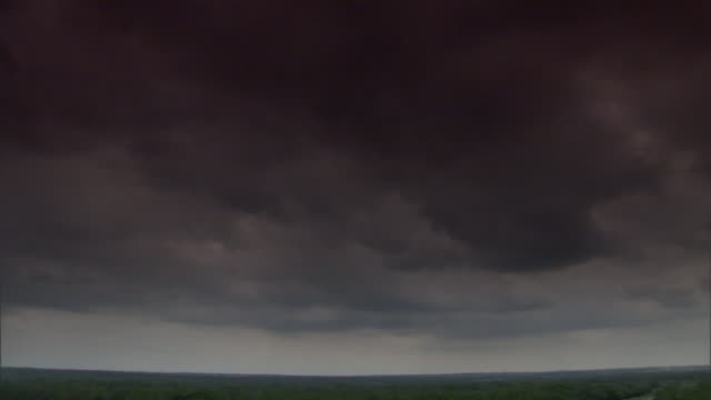 storm clouds drift along the horizon. - ominous stock videos & royalty-free footage