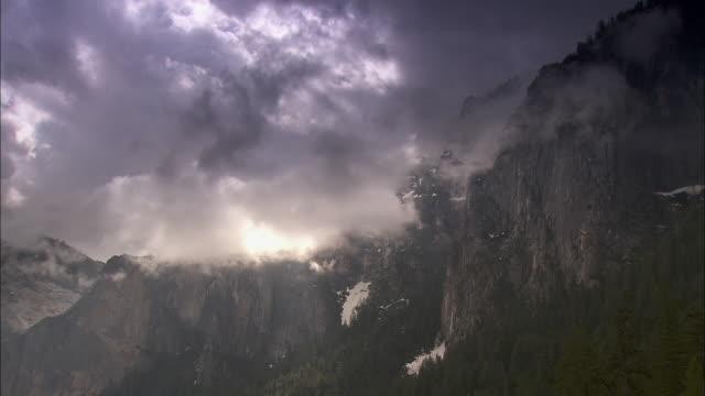 vídeos de stock e filmes b-roll de storm clouds drift over mountains in the yosemite national park. - paredão rochoso