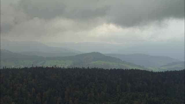 aerial ws storm clouds floating above forest and hillls / lorraine, france - lorraine stock-videos und b-roll-filmmaterial