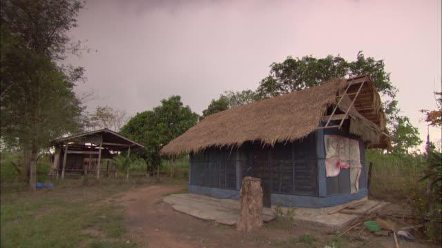 vídeos de stock e filmes b-roll de storm clouds hang over a hut with a thatched roof in malaysia. - telhado de palha