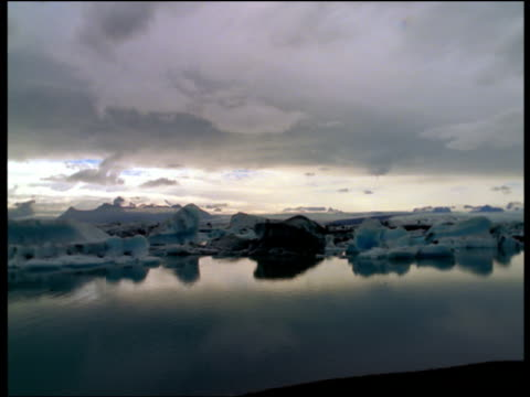 Storm clouds hang over a lake with large chunks of ice.
