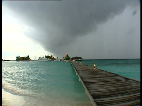 storm clouds hanging over the maldives - strohdach stock-videos und b-roll-filmmaterial