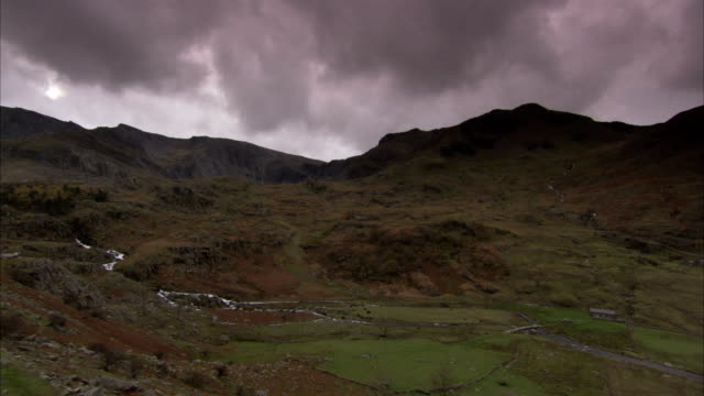 storm clouds hover over a valley in wales. available in hd. - wales stock videos & royalty-free footage