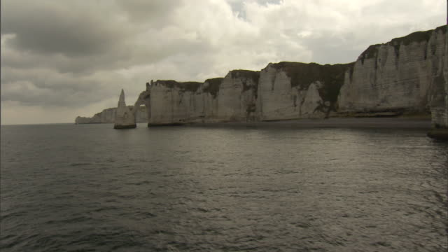 storm clouds loom above sheer cliffs in france. - natural arch stock videos & royalty-free footage