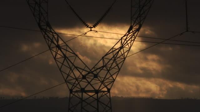 storm clouds loom behind a pylon. - traliccio elettrico video stock e b–roll