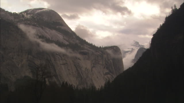 storm clouds loom over mountains at yosemite national park in california. - カリフォルニアシエラネバダ点の映像素材/bロール