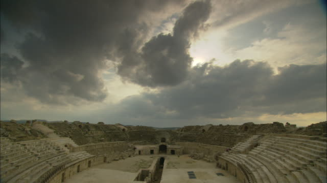 Storm clouds loom over the ruins of the Oudna Amphitheater in Tunisia.