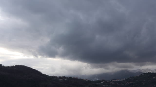 Storm clouds mass over distant village and mountains