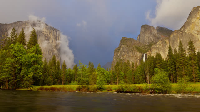 vídeos de stock, filmes e b-roll de time lapse wide shot storm clouds move over el capitan and bridalveil fall in yosemite valley with merced river in foreground - sierra nevada da califórnia