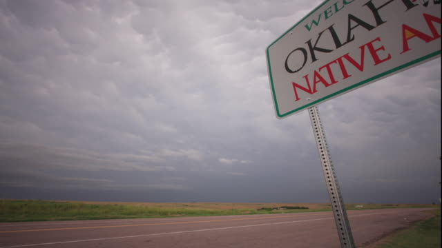 ws pan t/l storm clouds move rapidly in overcast sky above road, fields and 'welcome to oklahoma' sign / oklahoma, usa - oklahoma stock-videos und b-roll-filmmaterial