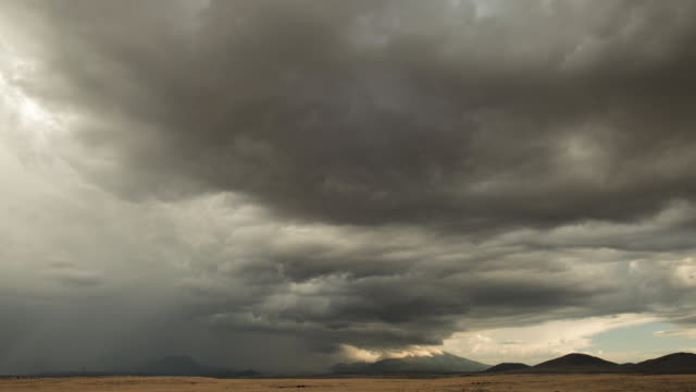 ws t/l storm clouds moving above field with mountains in distance / flagstaff, arizona, usa - flagstaff arizona video stock e b–roll