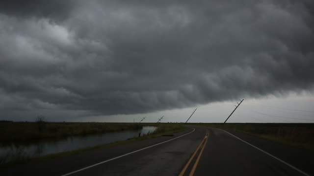 storm clouds over bending power line along road after after hurricane laura passed through holly beach, louisiana, u.s., on friday, august 28, 2020. - bending over stock videos & royalty-free footage