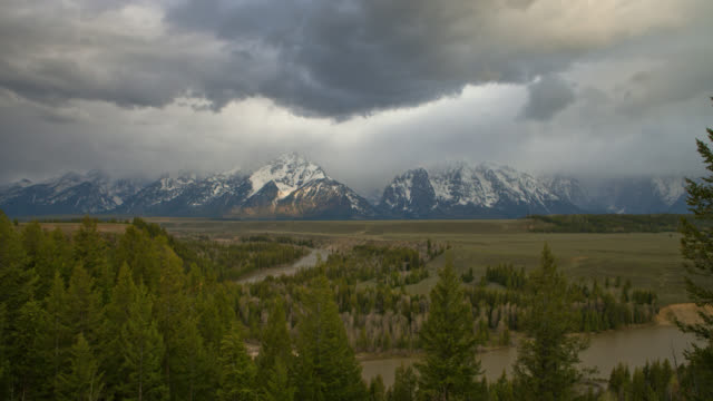 time lapse high angle long shot storm clouds over snake river, plains, and snowy tetons in wyoming - スネーク川点の映像素材/bロール
