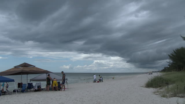 storm clouds overtaking a beach, florida gulf coast - naples florida stock videos & royalty-free footage