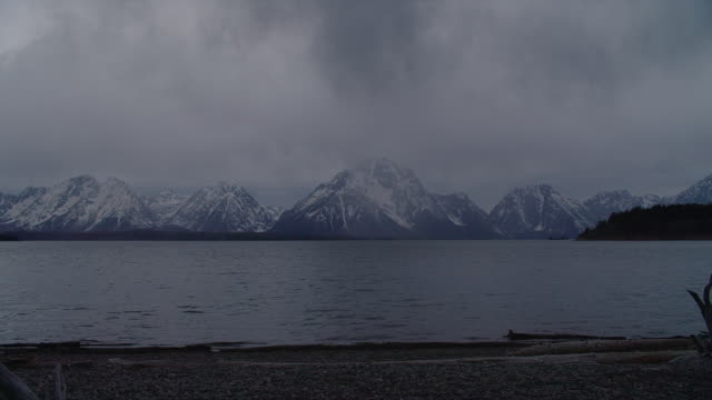 wide pan storm clouds partially obscuring mt moran and teton range with snake river in foreground, grand teton national park, wyoming - mt moran stock videos & royalty-free footage