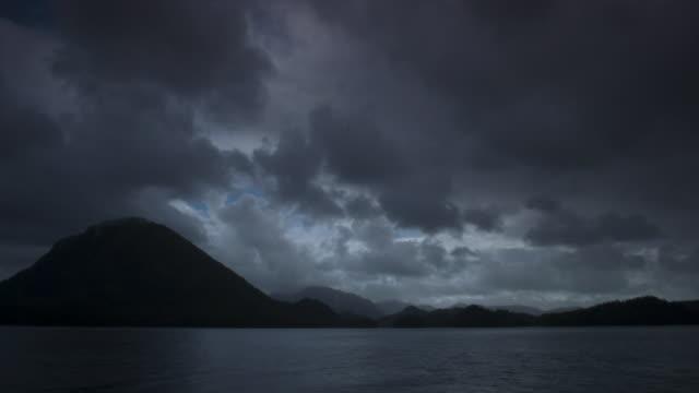 Storm clouds pass over mountainous coast, rain falls on lens.