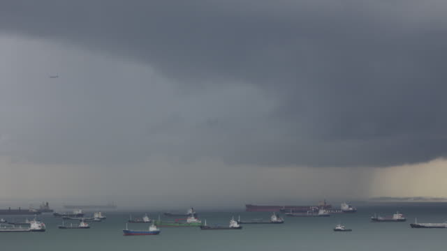 Storm clouds quickly pass over cargo ships in a harbor.