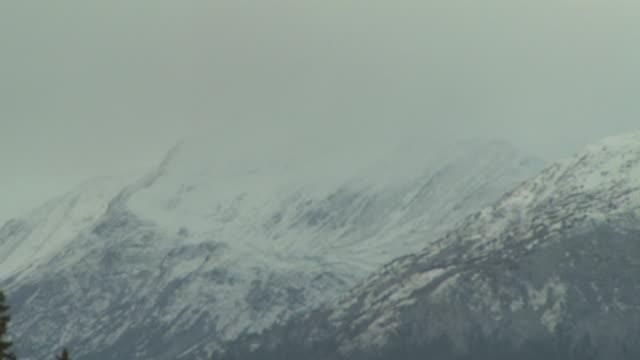 vídeos de stock e filmes b-roll de storm clouds race across snowy mountain peaks. - alasca