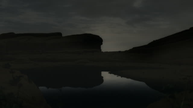 Storm clouds race over a valley where a dinosaur lies dying in a computer generated animation.