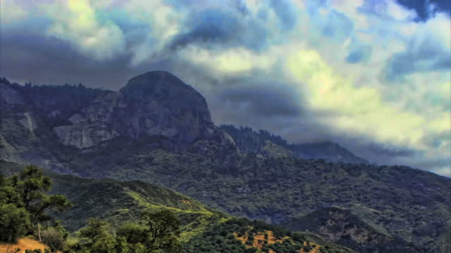 storm clouds roil above a giant rock in the mountains. - digital enhancement stock videos & royalty-free footage