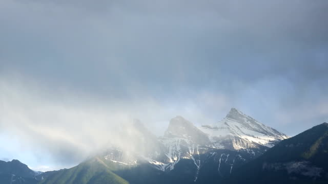 storm clouds swirl around mountain peaks - alberta stock videos & royalty-free footage