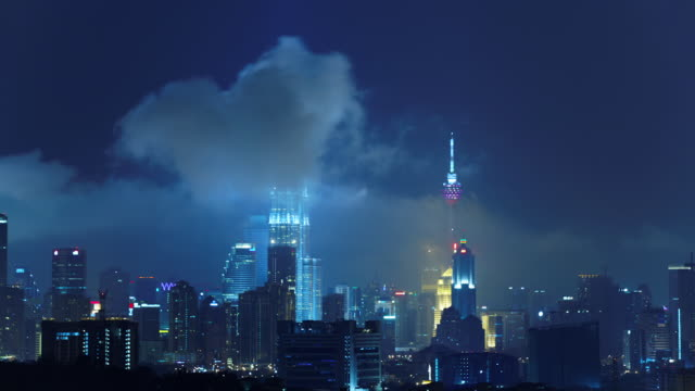 storm clouds swirl around the kuala lumpur skyline at night. - petronas twin towers stock-videos und b-roll-filmmaterial