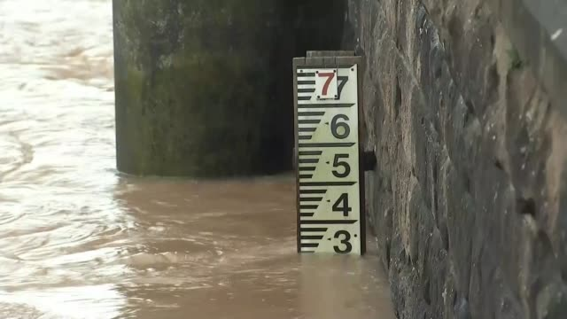 monmouth flood scenes wales monmouth ext high river flowing under bridge / water level meter / fast flowing river / flooded trees and building /... - wales stock videos & royalty-free footage