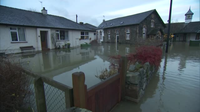 flooding in cumbria england cumbria keswick ext flooded houses people wading along flooded street children playing on piles of debris left by... - itv weekend lunchtime news点の映像素材/bロール
