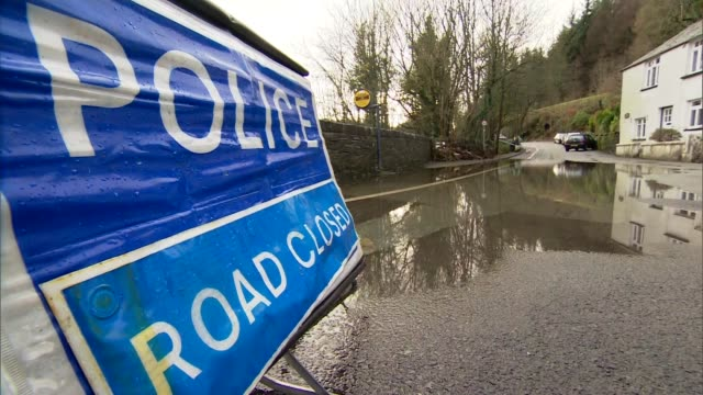 impact in north of england / david cameron visits cumbria england cumbria ext fastflowing floodwater going under bridge sign 'police road closed' in... - cumbria stock-videos und b-roll-filmmaterial