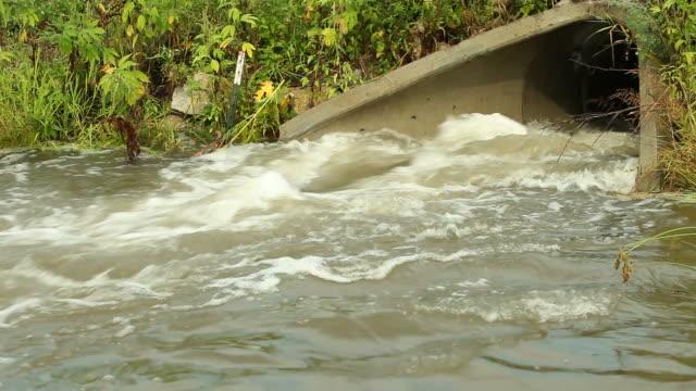 vídeos de stock, filmes e b-roll de de drenagem para tempestades culvert com maravilhosas água abaixo road - drenagem