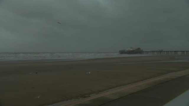 Storm Eleanor causes damage across UK Lancashire Blackpool SEQUENCE TIMELAPSE deserted beach inder heavy grey sky with pier in distance