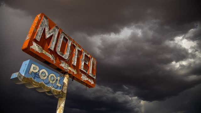 storm gathering over rustic motel sign - time lapse - condizione negativa video stock e b–roll