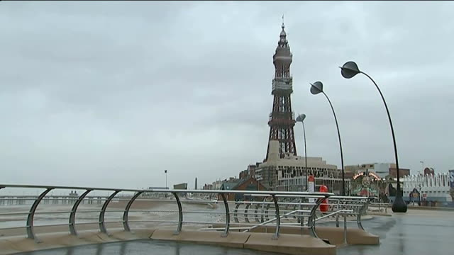 vídeos de stock, filmes e b-roll de blackpool man putting chain across entrance to pleasure beach as blown about by wind blackpool pleasure beach and tower as heavy winds blow rough sea... - aberystwyth