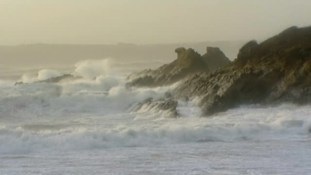 pembrokeshire west angle bay ext gvs waves crashing ashore and rough sea during storm girl leaning into the wind and being held upright and teenage... - bay window stock videos & royalty-free footage