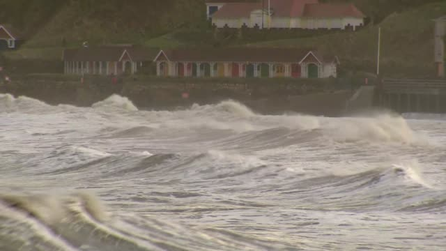 stockvideo's en b-roll-footage met storm on scarborough seafront storm on scarborough seafront england north yorkshire scarborough ext people laying sandbags on seafront shops / heavy... - scarborough engeland