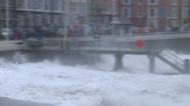 aberystwyth various shots waves from storm ophelia crashing against seafront and flooding into street - aberystwyth stock videos & royalty-free footage
