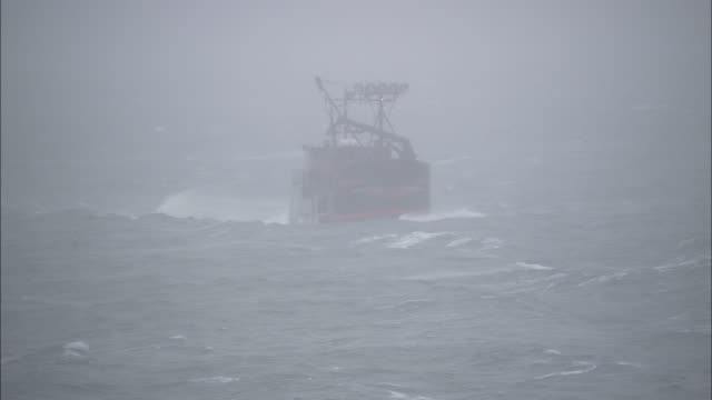 a storm rages around a fishing boat. - ship stock videos & royalty-free footage