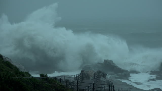 Storm surge waves at high tide crash into rock coastline of Japan as typhoon Shanshan hits