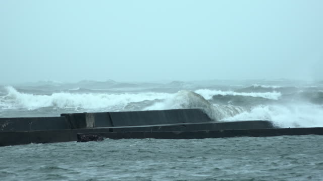 Storm surge waves at high tide over spill a sea wall as typhoon Shanshan affects Japan