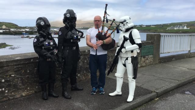 storm trooper and tie fighter pilot characters guard a bagpipe player during the first ever star wars festival taking place against the backdrop of... - evil stock videos and b-roll footage