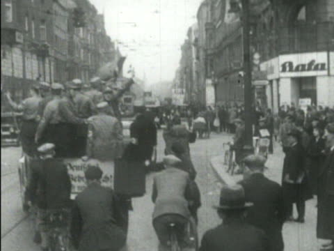 germany sturmabteilung storm troopers crowded into open truck riding up busy german street w/ bicycle riders behind some holding onto back people... - nazi brown shirts stock videos & royalty-free footage